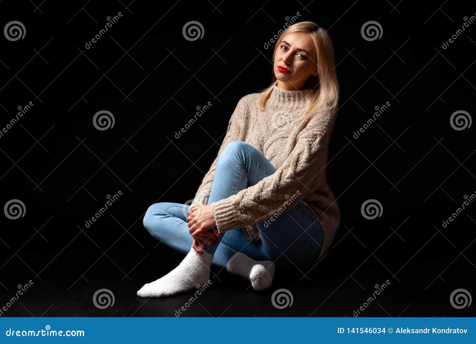 Una muchacha rubia se sienta en el piso en el estudio en un fondo negro en vaqueros, un suéter y se cruzan los calcetines, sus pi