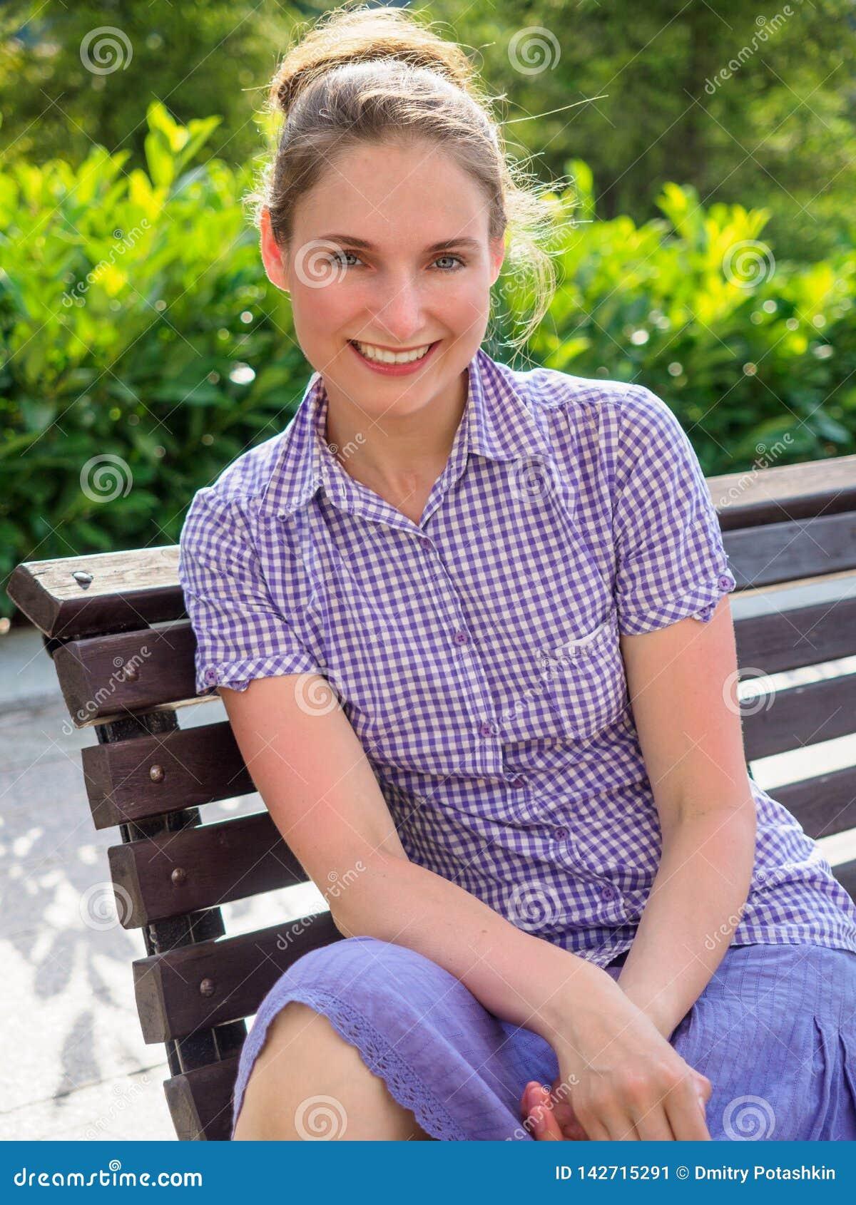 Una muchacha se sienta con una sonrisa en un banco en el parque del verano
