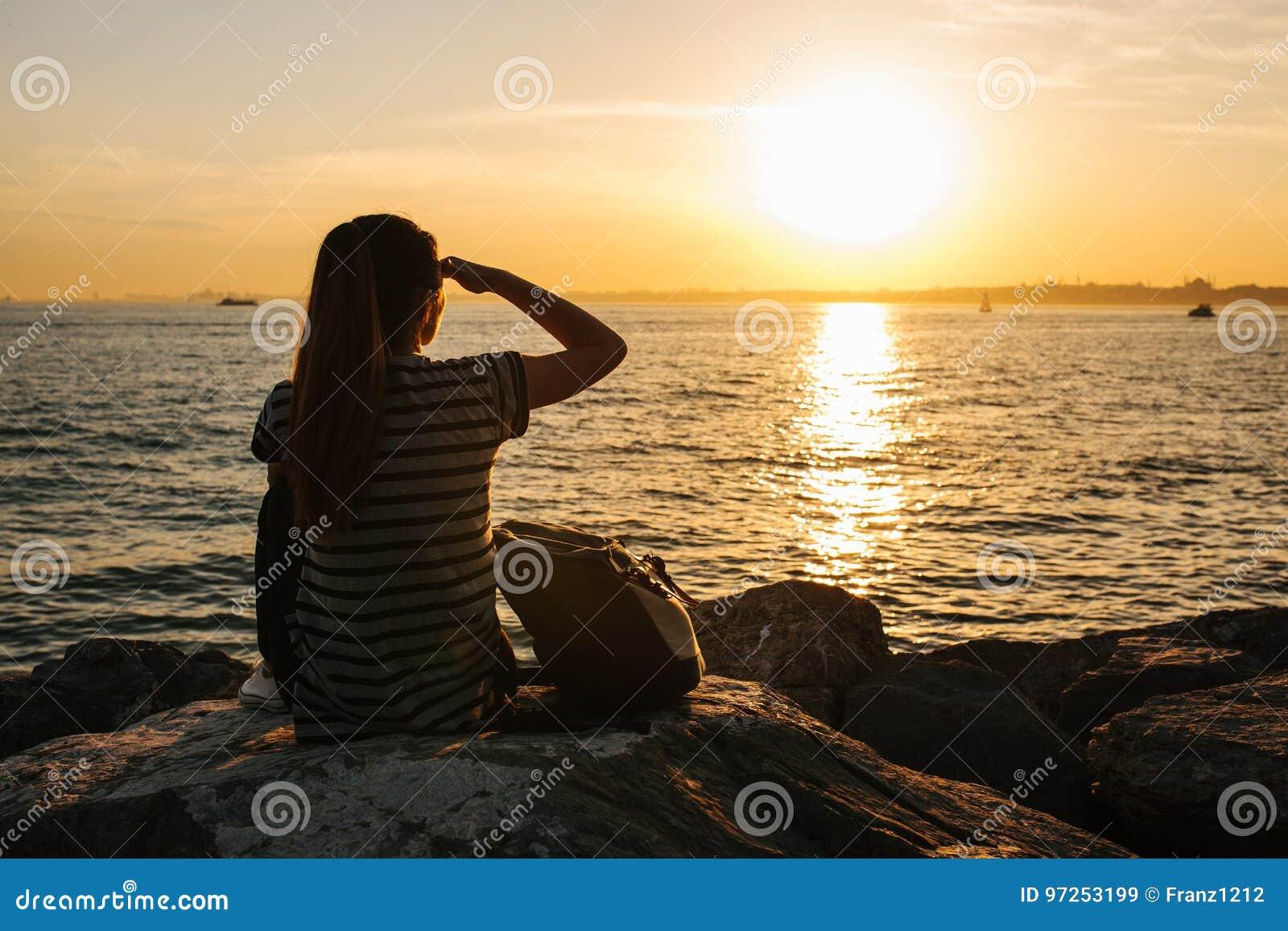 Una muchacha turística joven con una mochila se sienta en las rocas al lado del mar en la puesta del sol y mira en la distancia r