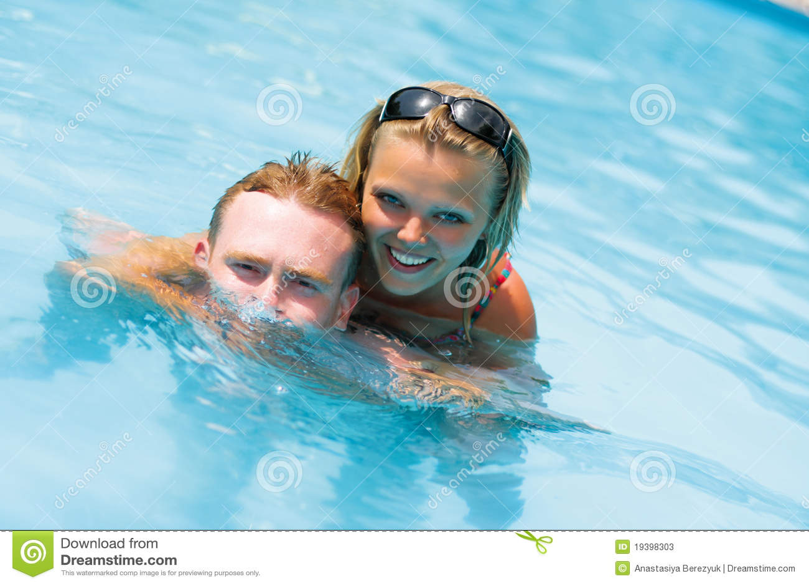 Una muchacha y un hombre está en agua azul