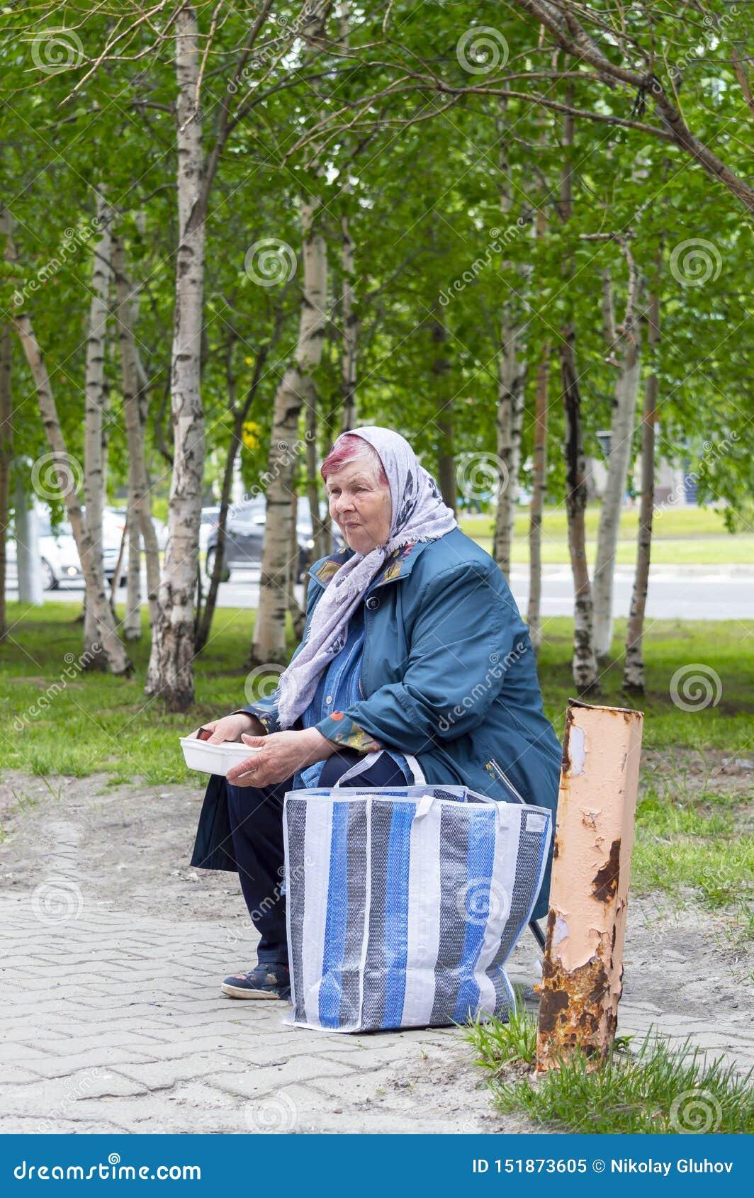 Una mujer adulta en bufanda pide donaciones Vista lateral