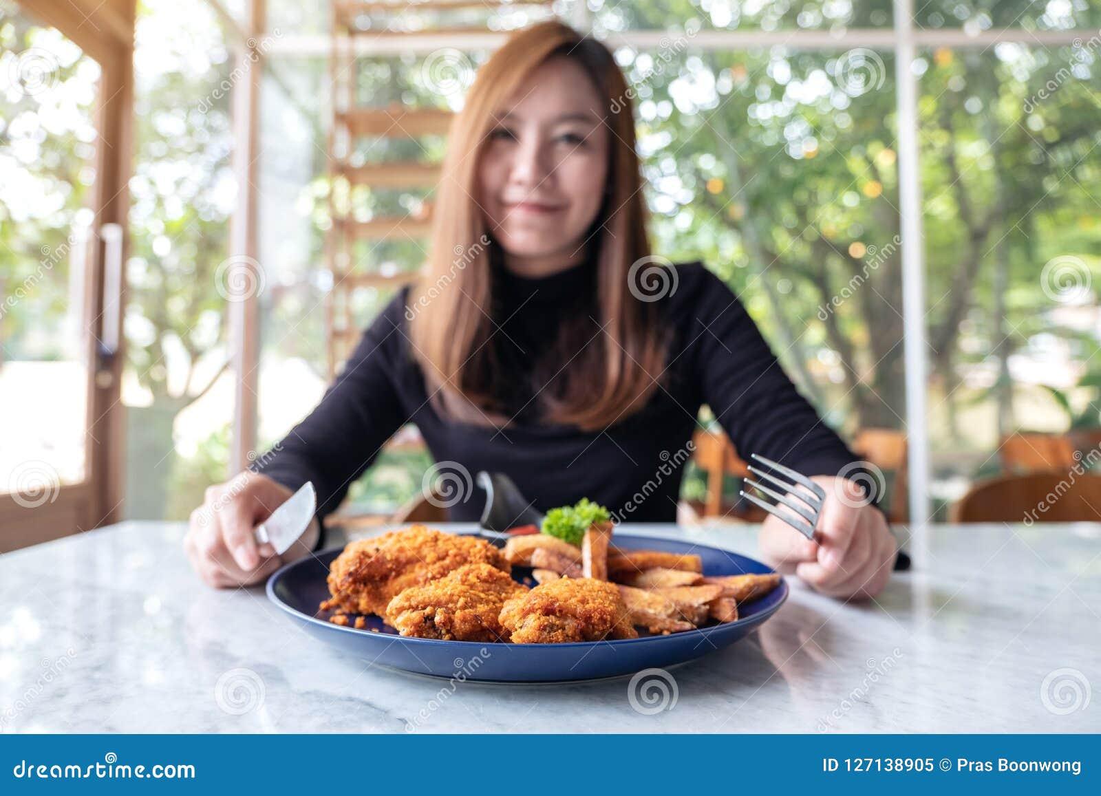 Una mujer asiática hermosa goza el comer del pollo frito y de las patatas fritas en restaurante