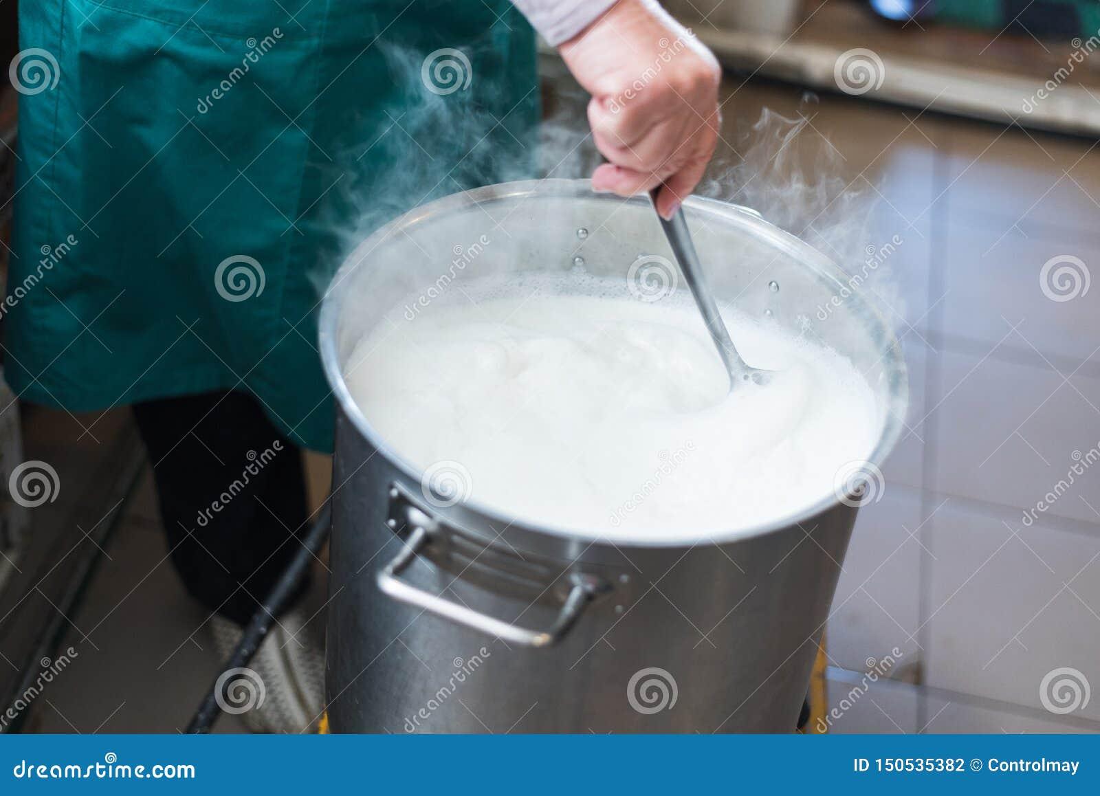Una mujer cocina la leche en una cuba y hace el requesón y el queso en casa Producción de queso en la granja