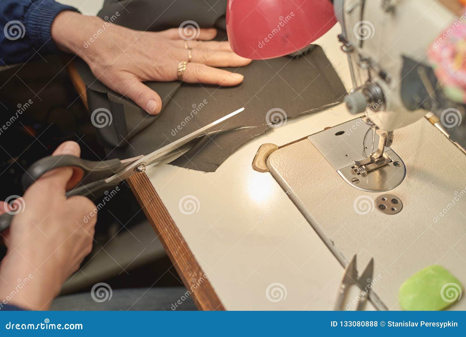 Una mujer corta el material antes de procesar en la máquina de coser