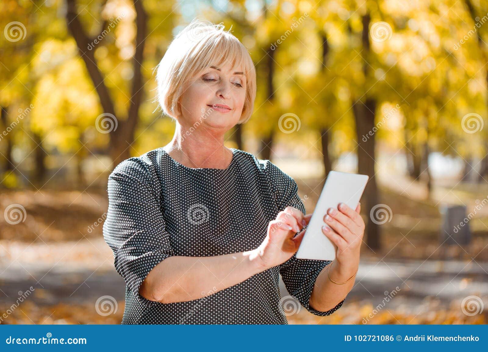 Una mujer de mediana edad atractiva que camina en un parque del otoño con los artilugios en un fondo borroso
