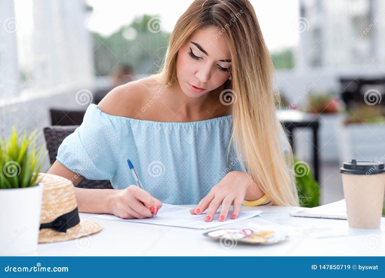 Una mujer de negocios, en verano en un restaurante del café, cumple adentro un contrato escrito, pone una firma en el contrato, h