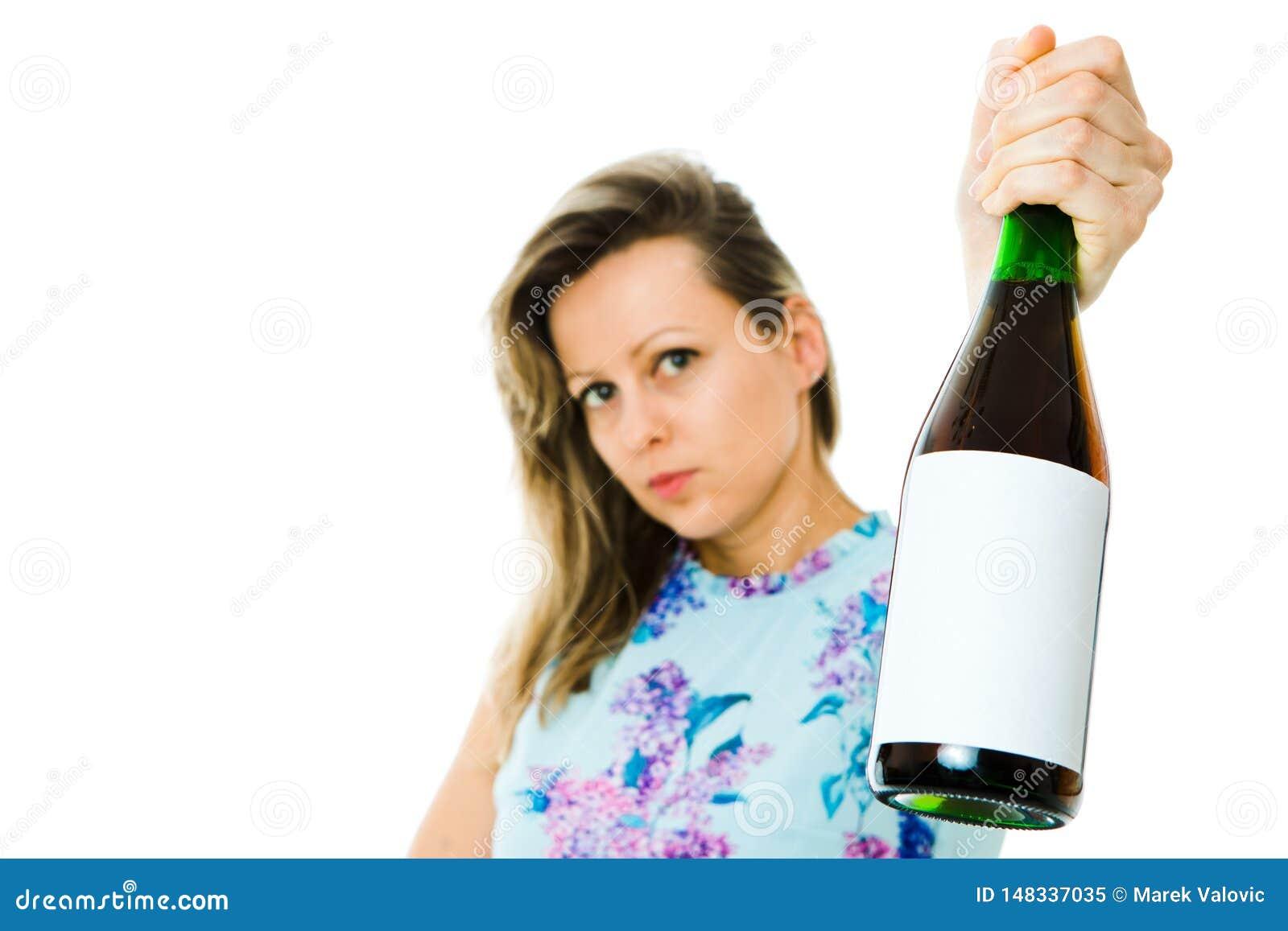 Una mujer en botella florecida de la tenencia del vestido de vino espumoso rojo - etiqueta en blanco