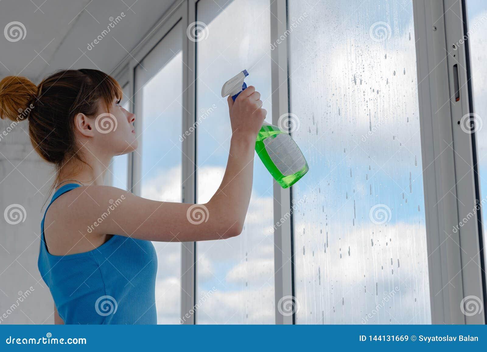 Una mujer en una camiseta azul lava una ventana