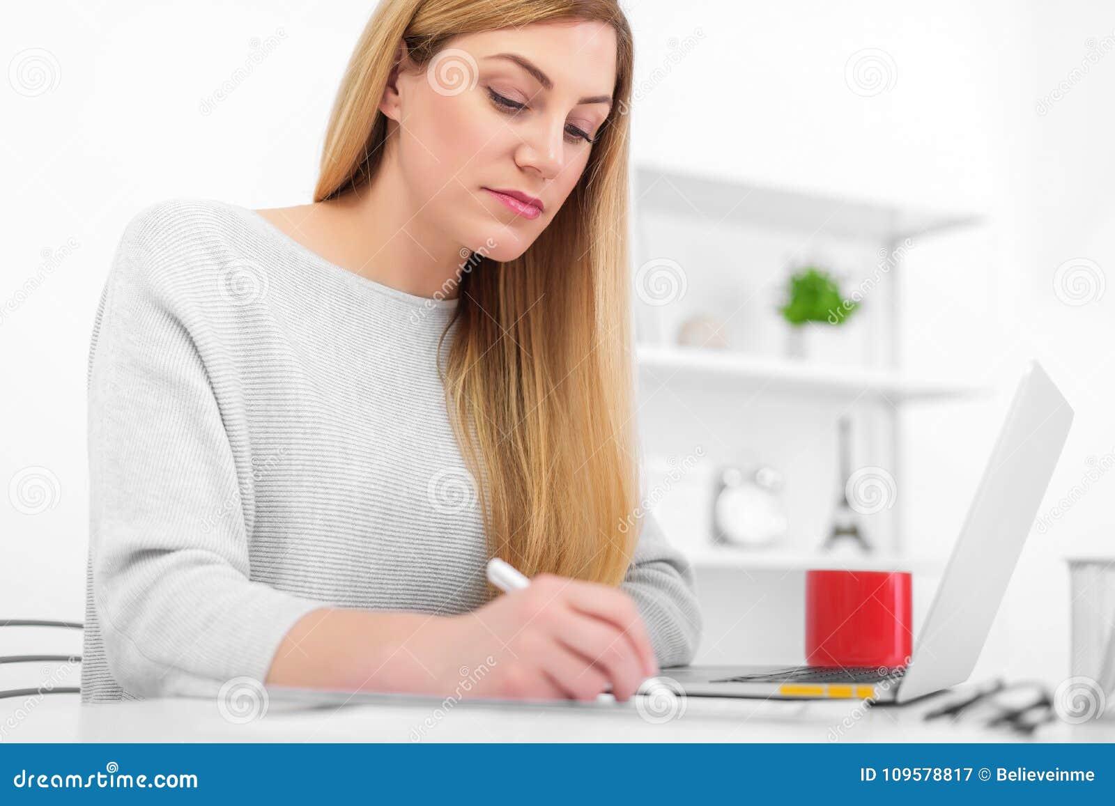 Una mujer en una oficina blanca se está sentando en una tabla y una escritura Una señora joven que usa un ordenador portátil llen