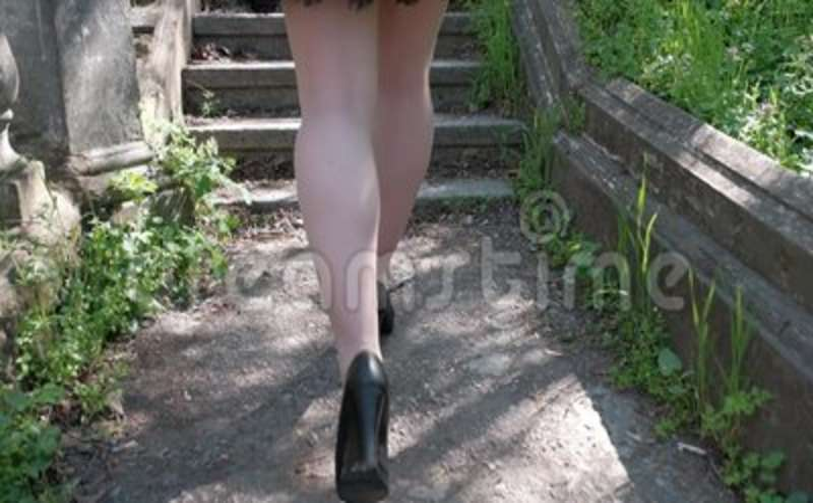 de40cadea Una mujer en zapatos negros con talones y una falda corta está subiendo una  escalera antigua.