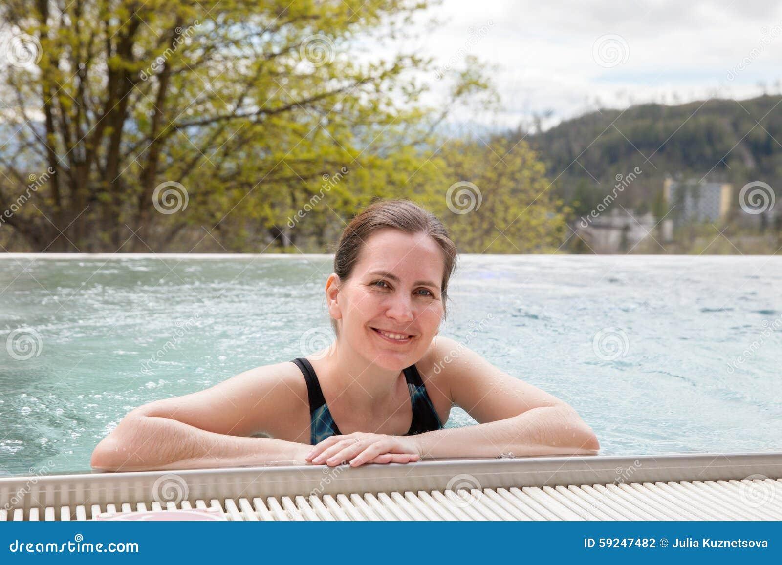 Una mujer está nadando en una piscina al aire libre en día de primavera