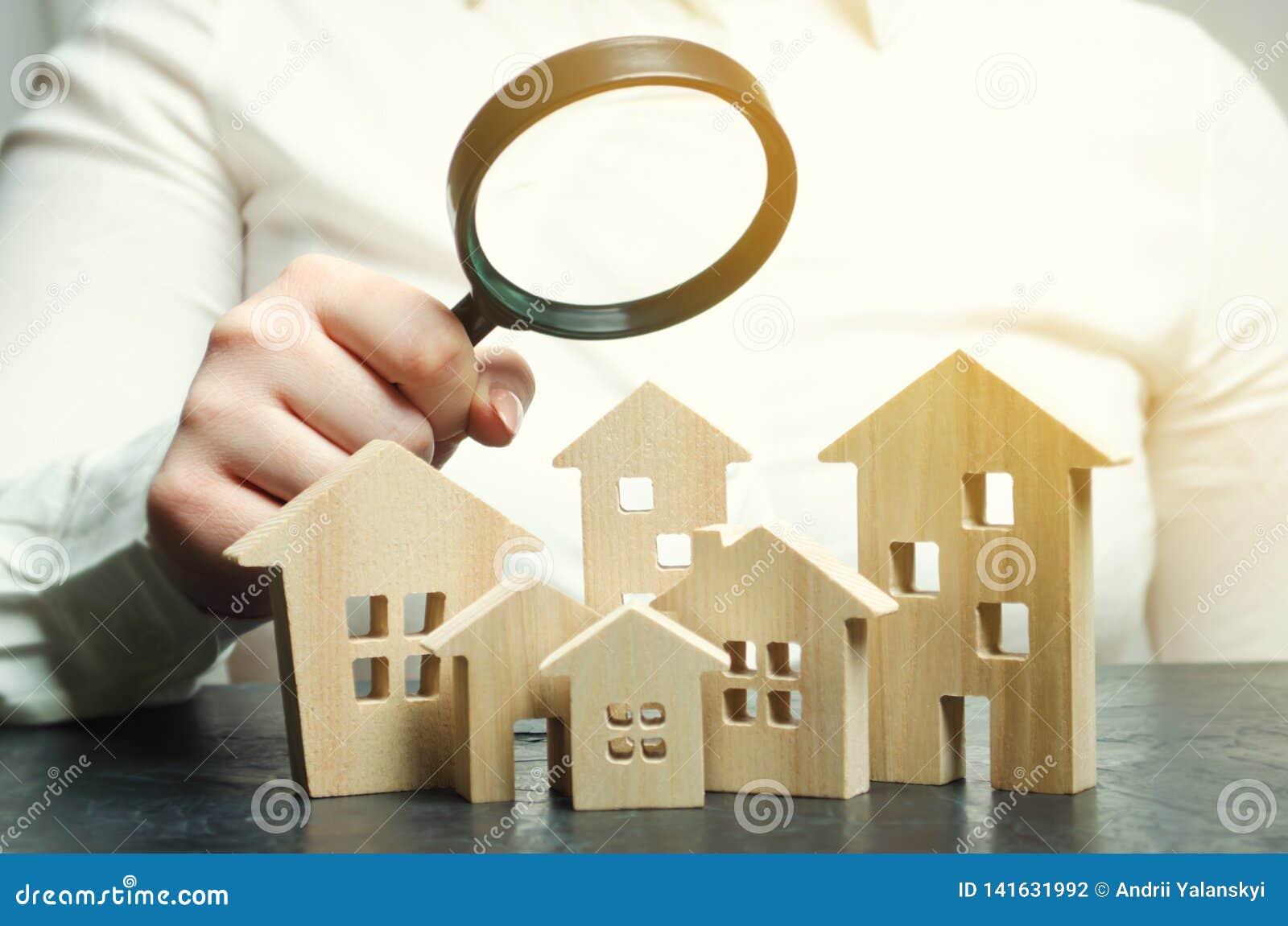 Una mujer está sosteniendo una lupa sobre las casas de madera Tasador de las propiedades inmobiliarias Evaluación/valoración de l