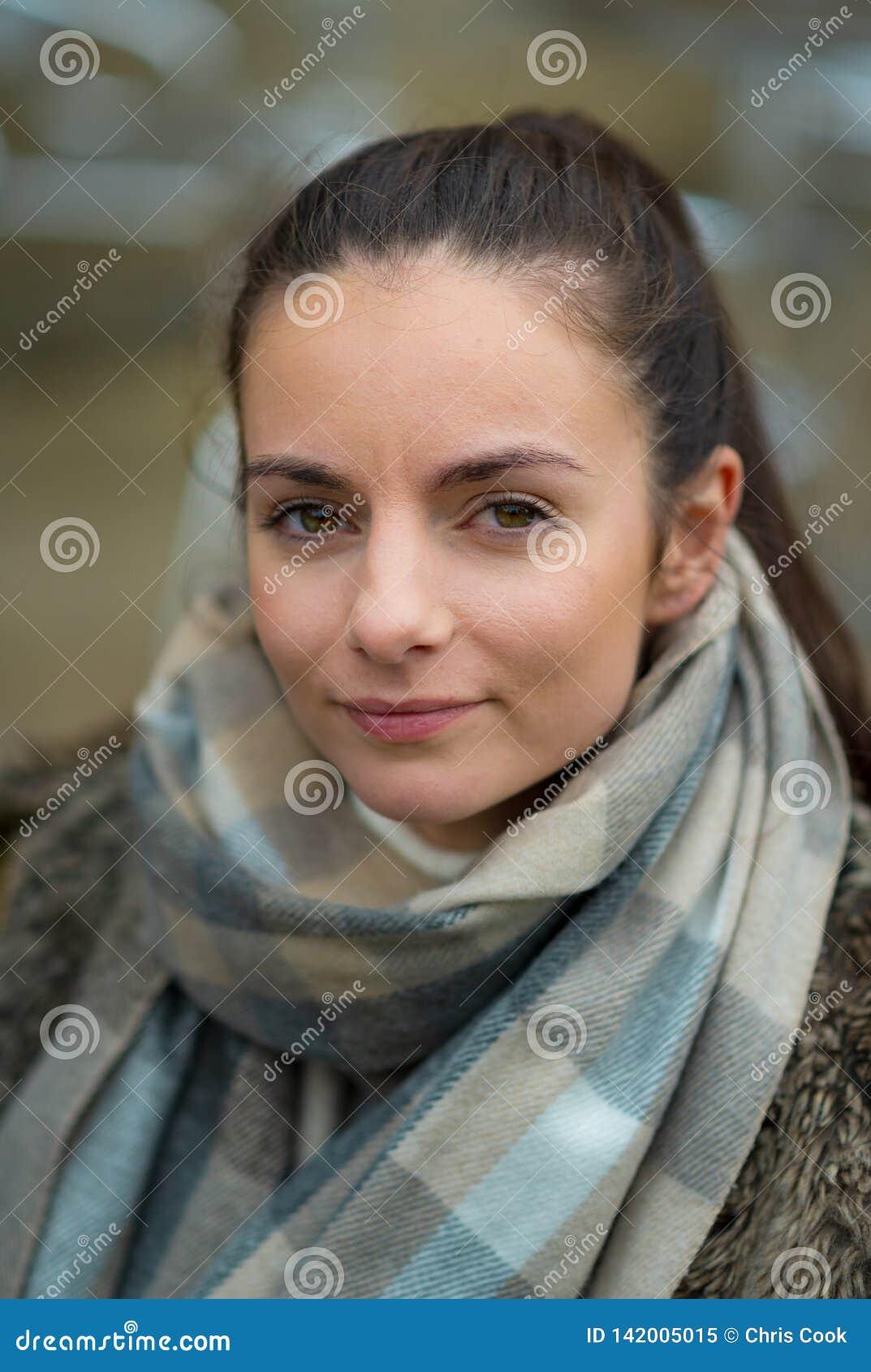 Una mujer femenina blanca joven mira la cámara vestida para el invierno