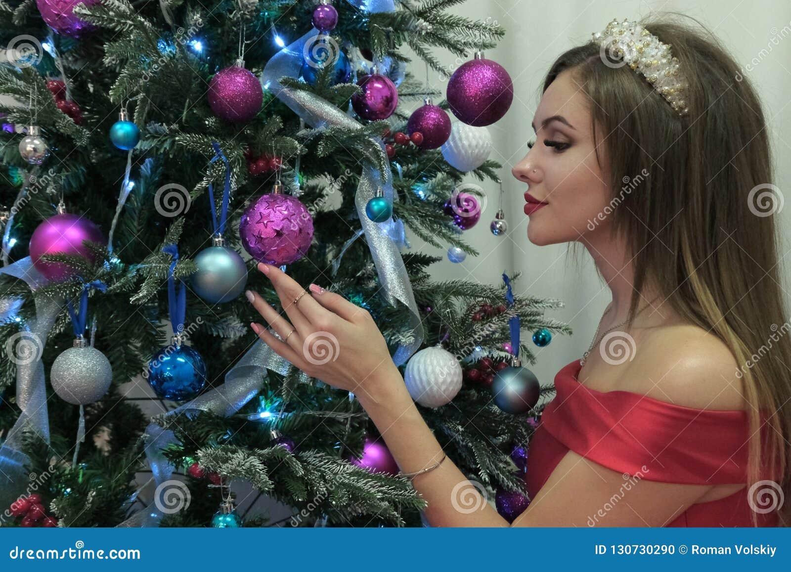 Una mujer hermosa cuelga para arriba los juguetes en un árbol del nuevo-año en un vestido rojo Tema de la Feliz Año Nuevo y de la