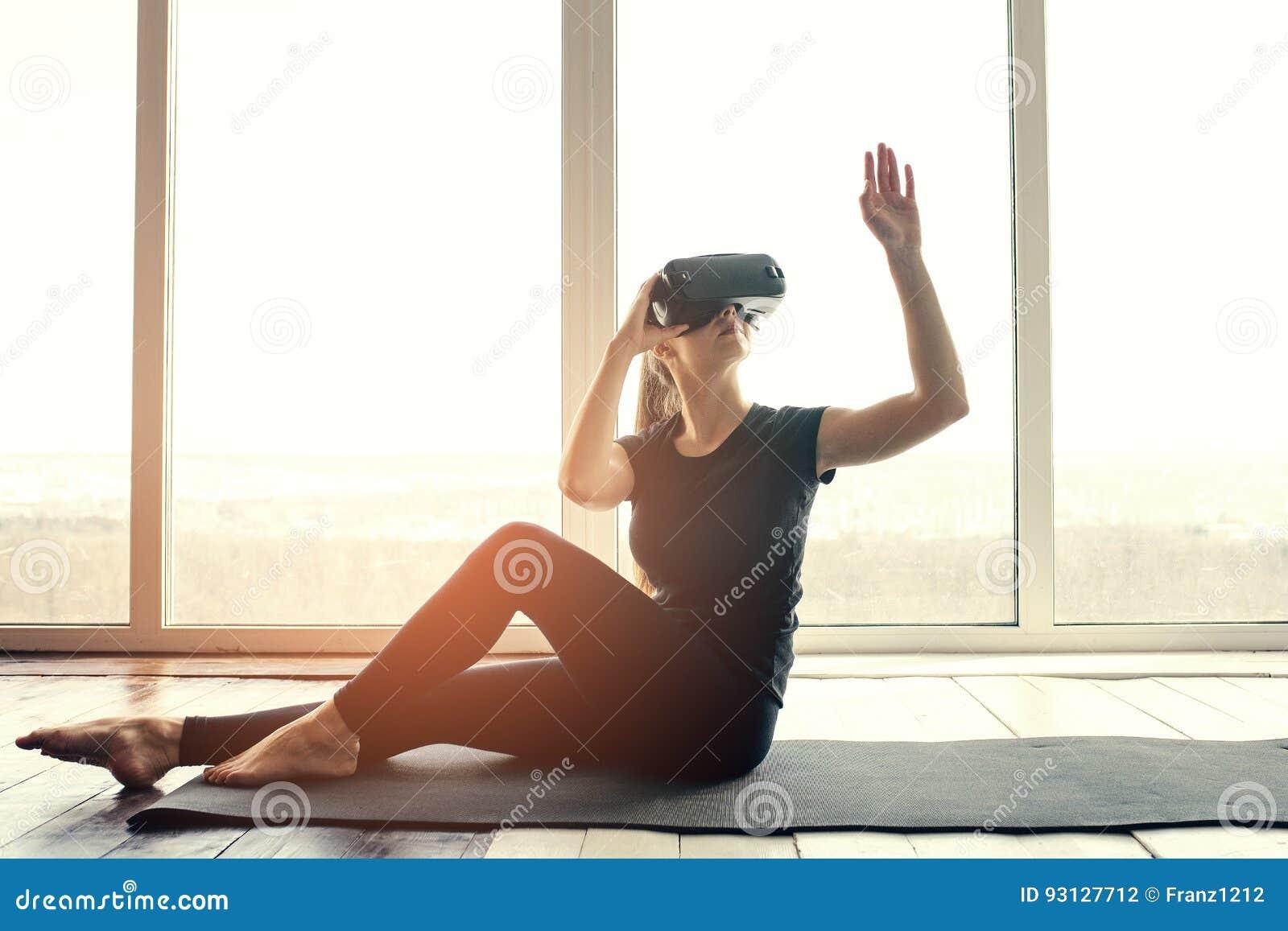 Una mujer hermosa joven en vidrios de la realidad virtual hace aeróbicos remotamente Concepto futuro de la tecnología Proyección