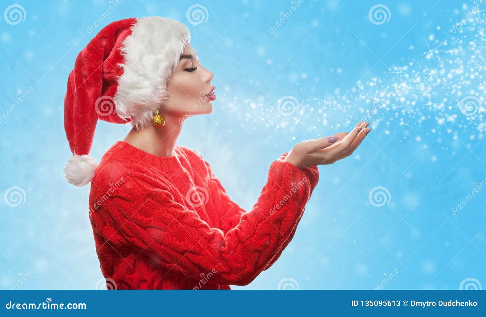 Una mujer joven atractiva está llevando un sombrero rojo de Santa Claus en su cabeza y en día de fiesta rojo un suéter sopla los