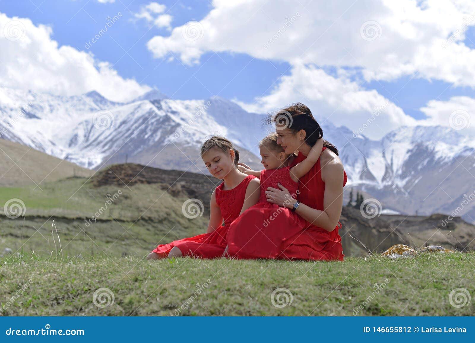 Una mujer joven con dos hijas en los vestidos rojos que descansan en las monta?as coronadas de nieve en la primavera