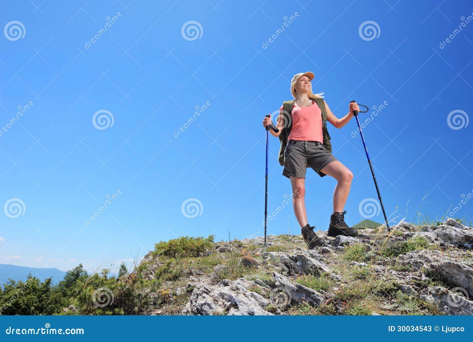 Una mujer joven con la mochila y caminar la presentación de los polos
