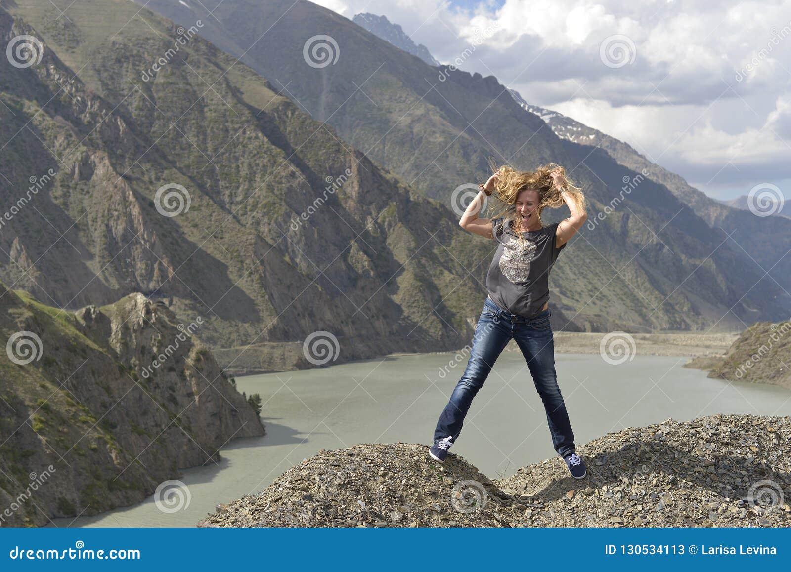 Una mujer joven con risas lanudas del pelo mientras que se coloca al borde de un acantilado sobre un lago