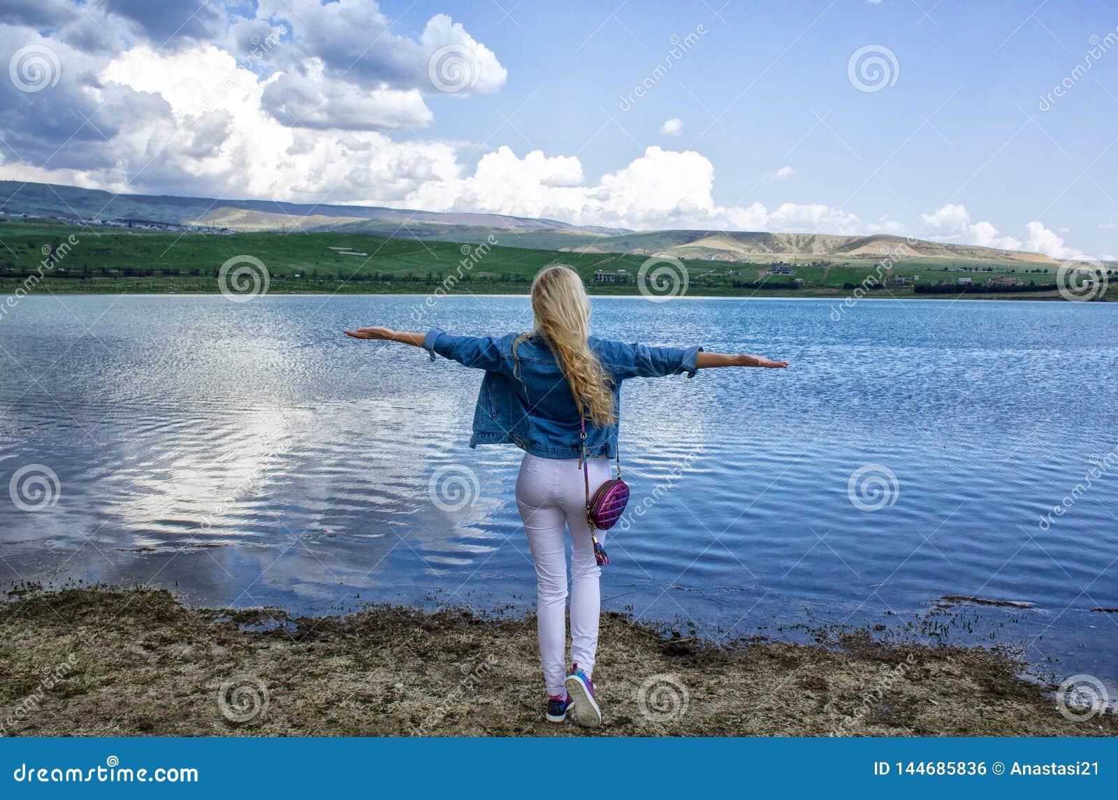 Una mujer joven delgada hermosa se coloca con su parte posterior en la orilla cerca del agua y admira el paisaje hermoso