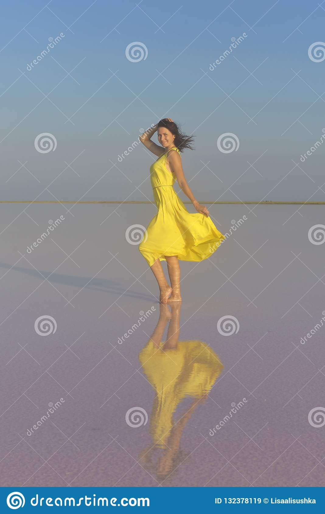 Una mujer joven en el medio de un lago de sal rosado se coloca en un vestido amarillo brillante y resuelve la puesta del sol