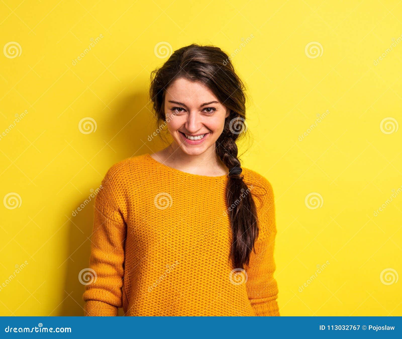 Una mujer joven en estudio en un fondo amarillo