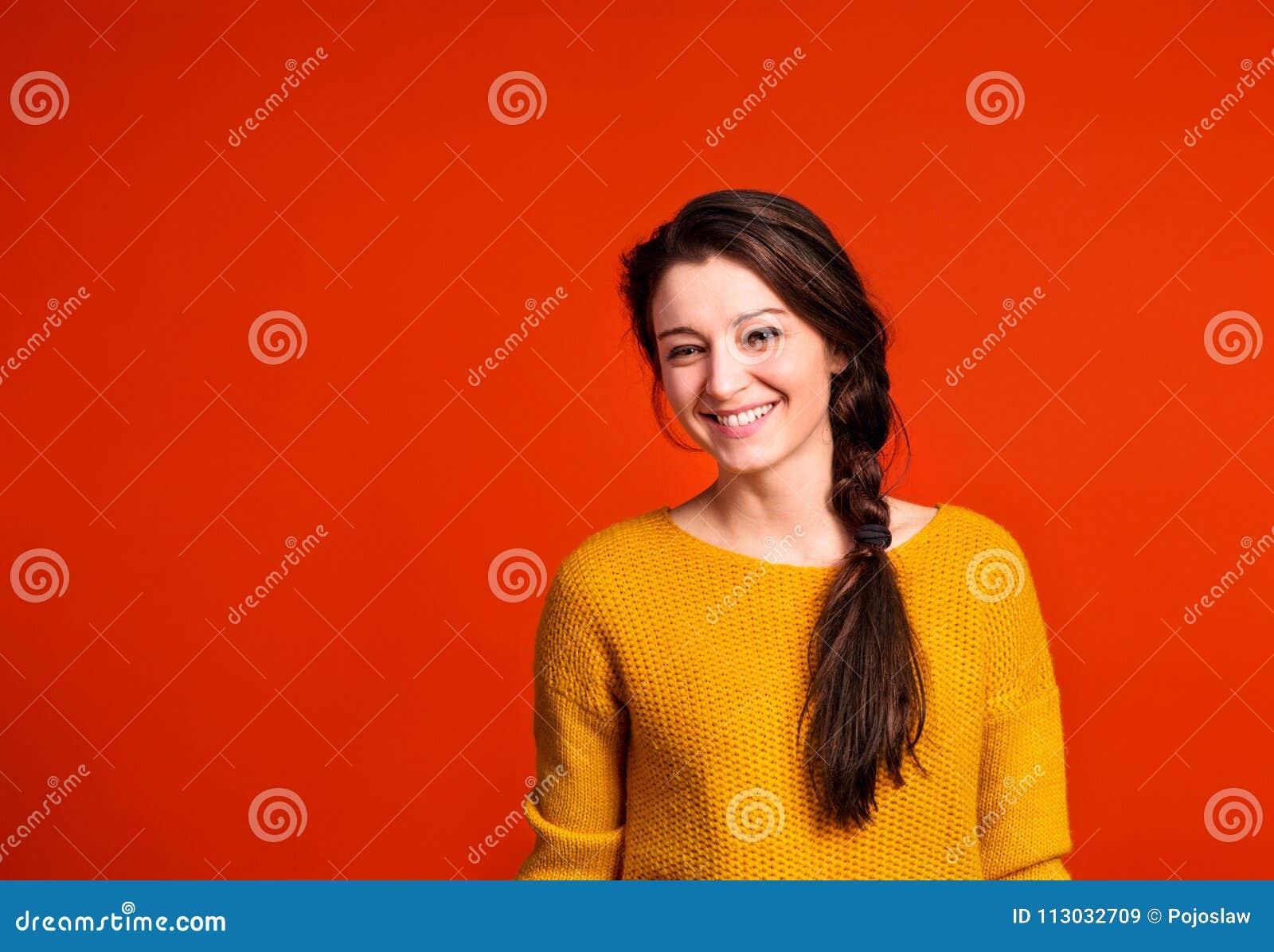 Una mujer joven en estudio en un fondo rojo