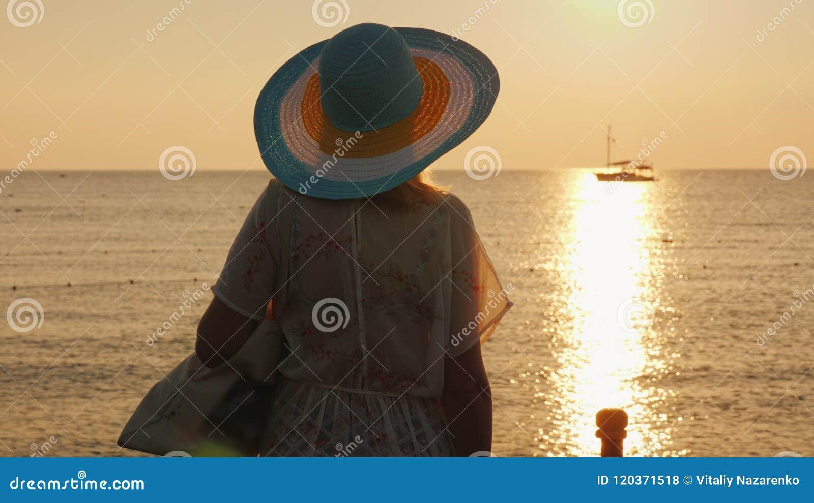 Una mujer joven en ropa de la playa y un sombrero de ala ancha está disfrutando de la salida del sol en la costa Visión trasera