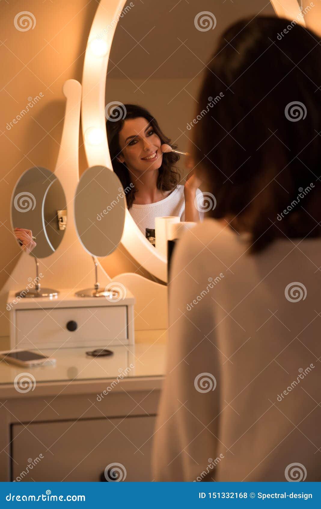 Una mujer joven hermosa en una tabla del maquillaje