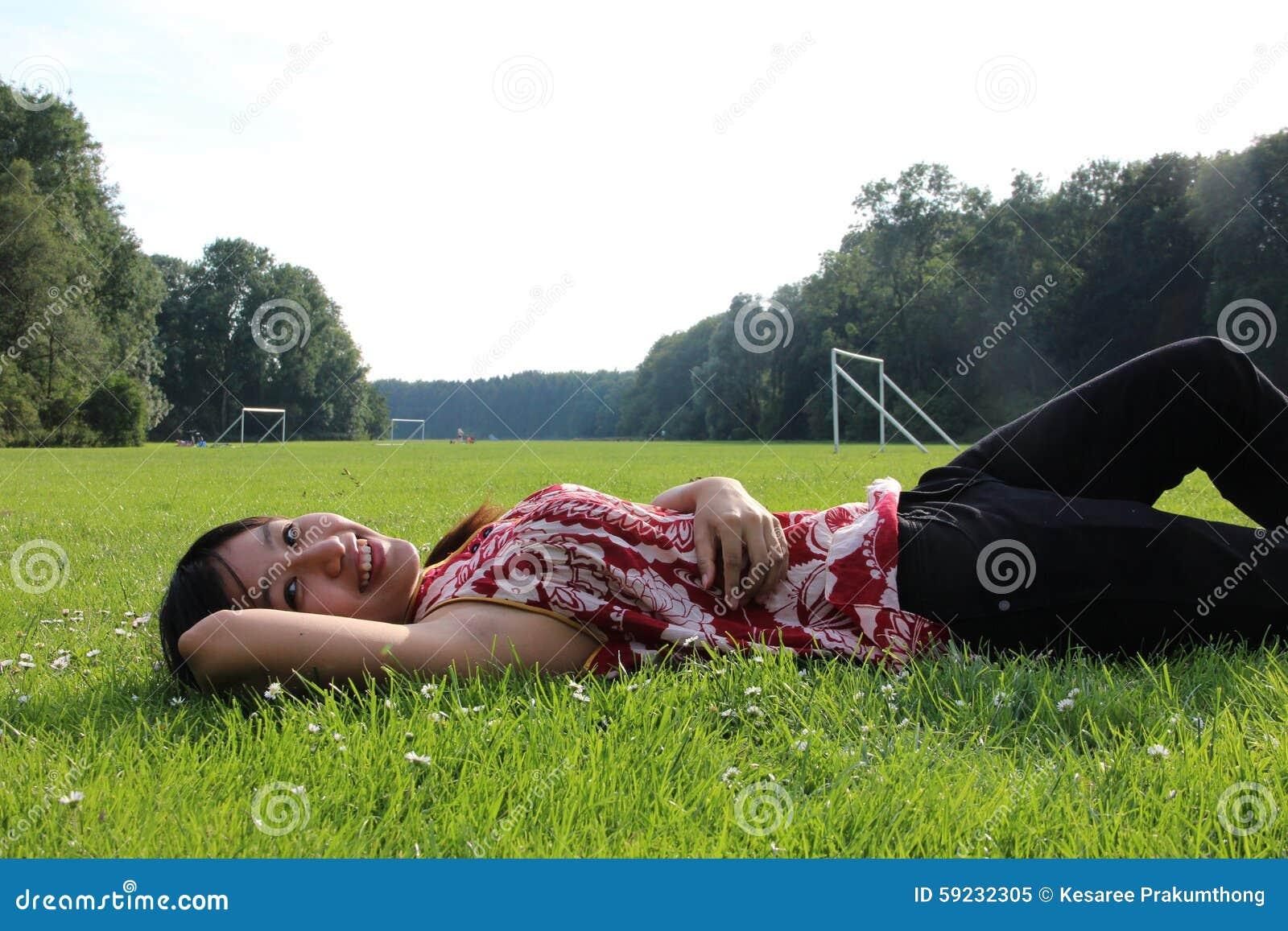 Una mujer joven que miente en un campo de hierba