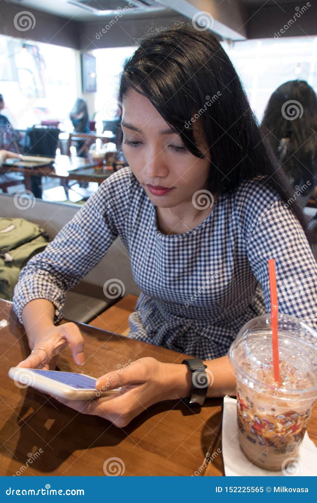 Una mujer joven que se sienta en un restaurante