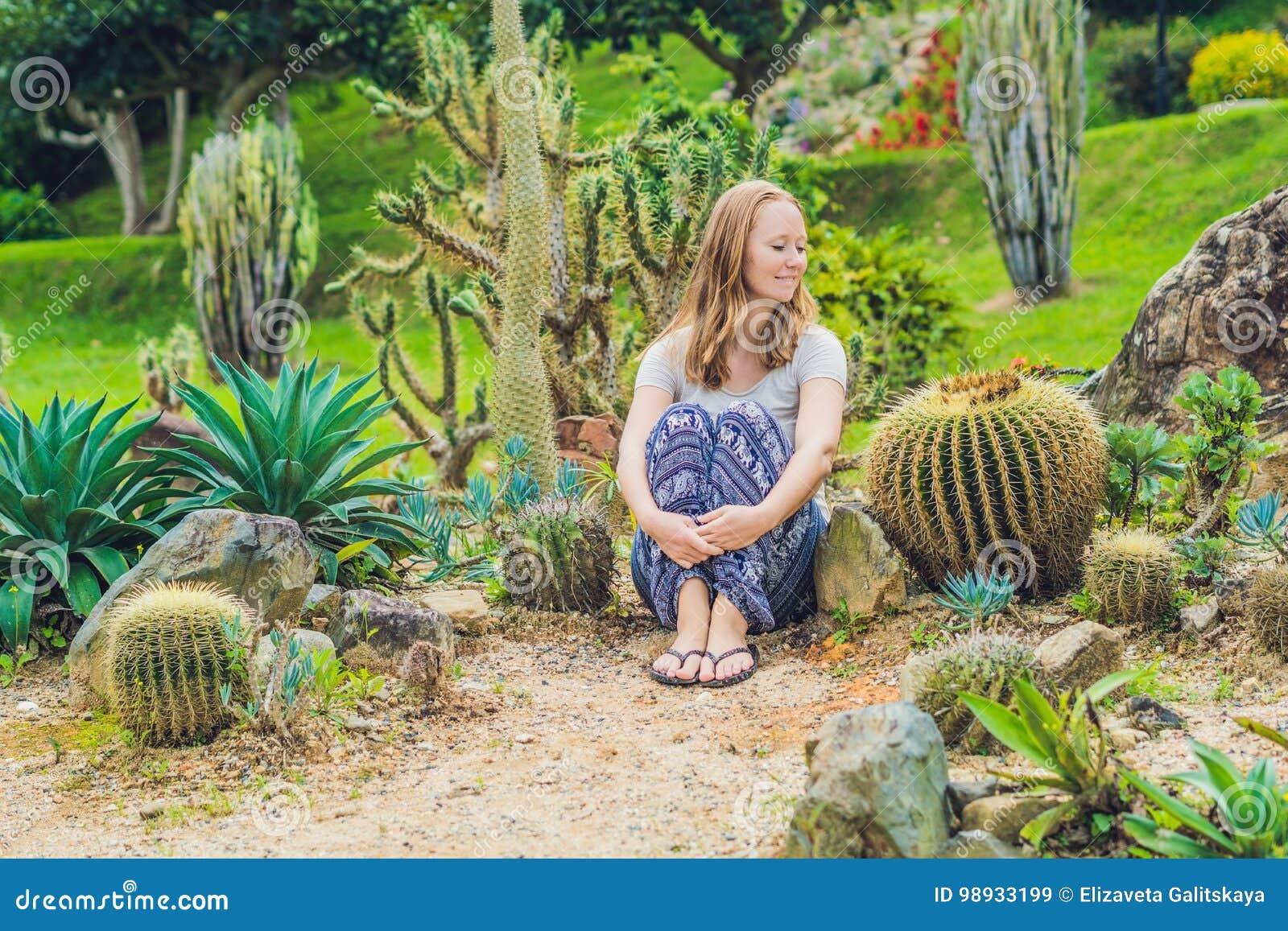 Una mujer joven se sienta en la tierra entre el cactus Concepto espinoso