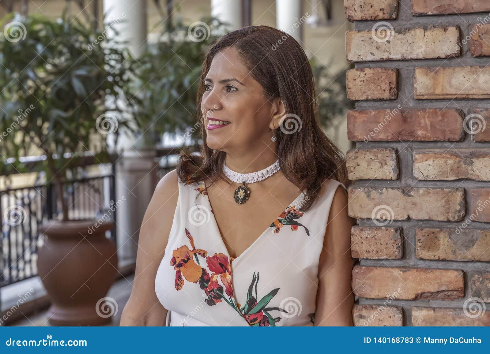 Una mujer madura latina sofisticada se inclina en una pared de ladrillo que mira lejos