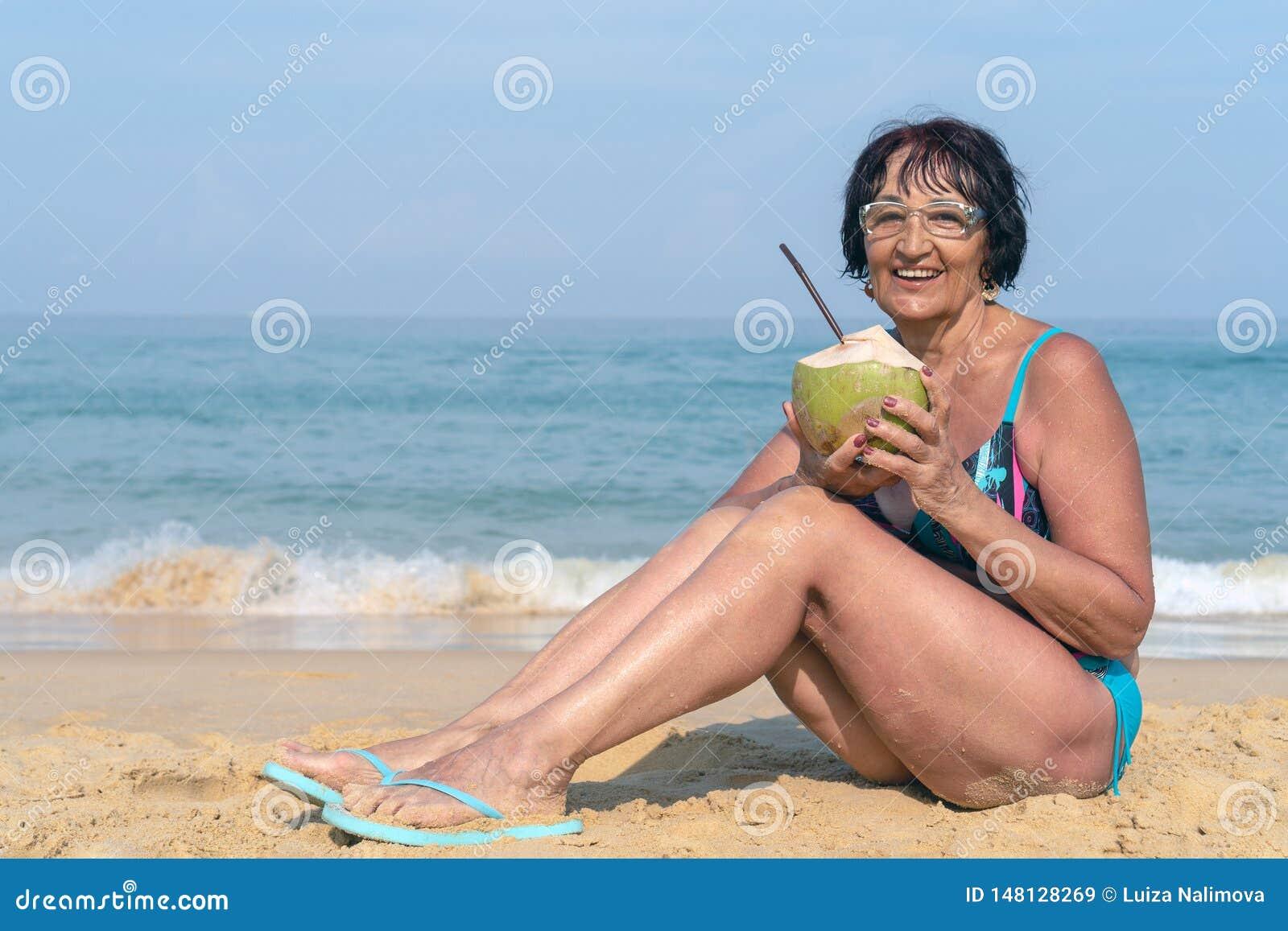 Una mujer mayor con el pelo negro se sienta por el mar en un día soleado Una mujer en un bañador con un coco está sonriendo