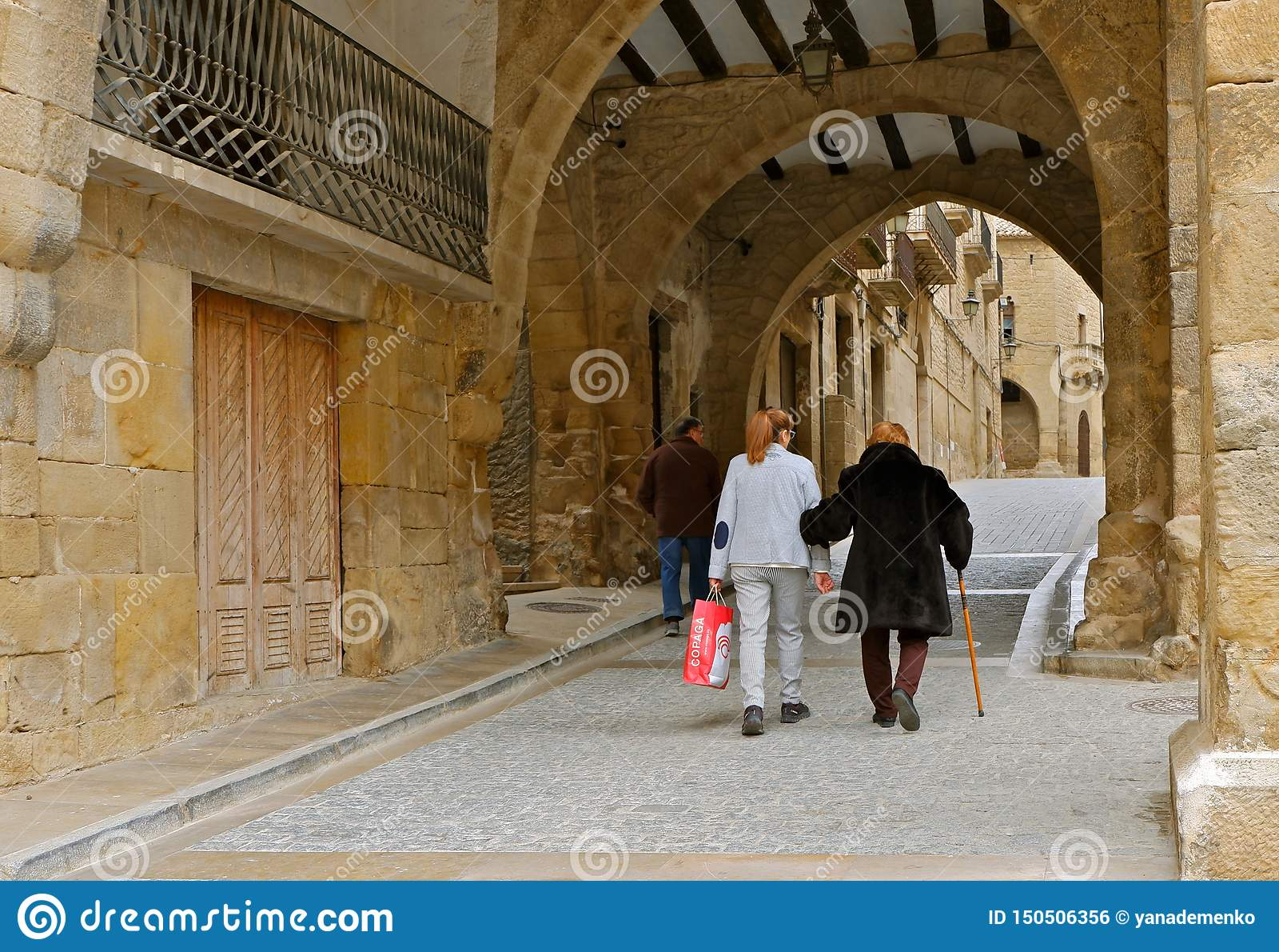 Una mujer mayor con un bastón y su familia están caminando abajo de la calle