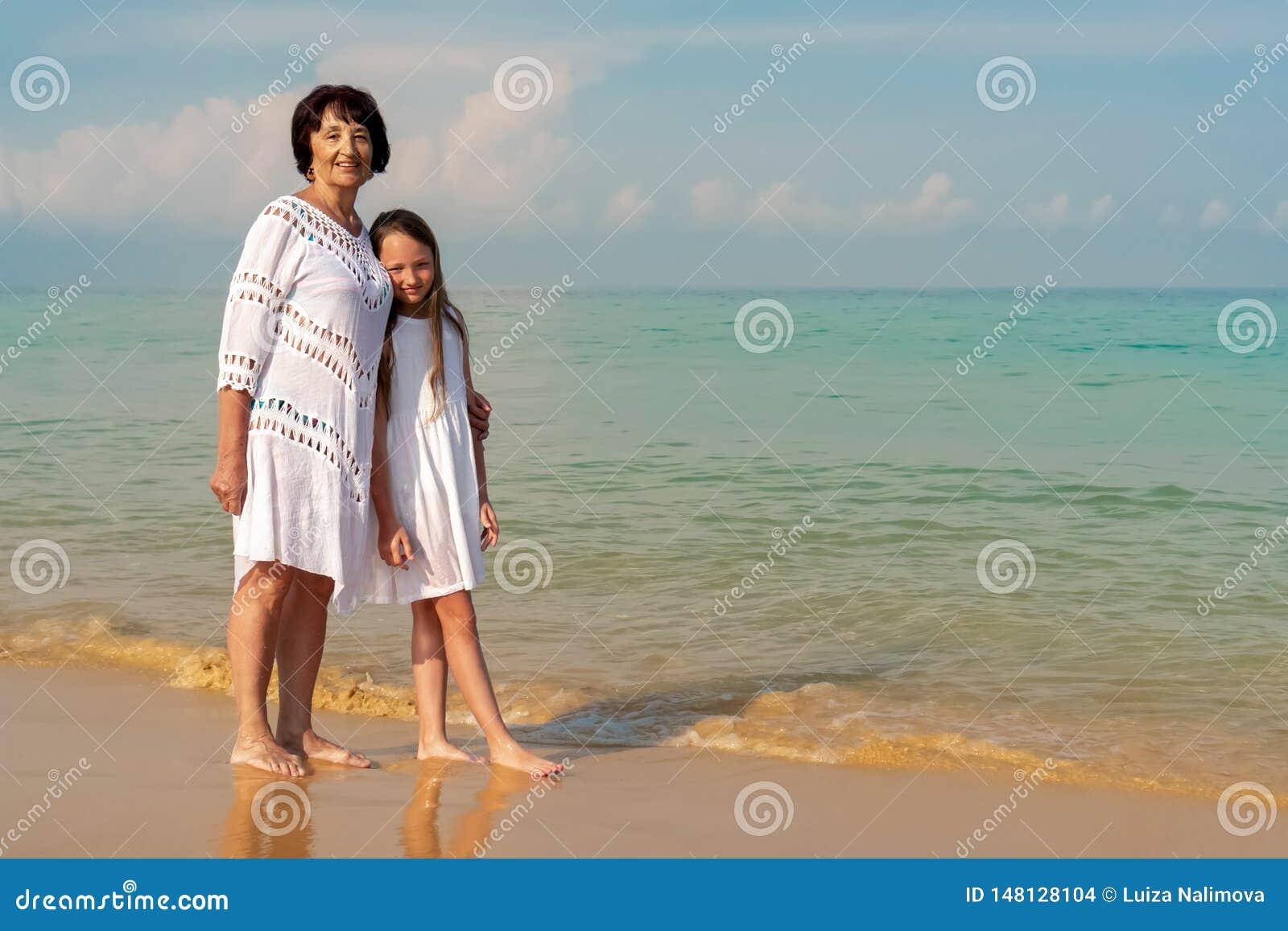 Una mujer mayor en un vestido blanco con una muchacha hermosa en un vestido blanco en el mar Concepto de verano soleado y feliz
