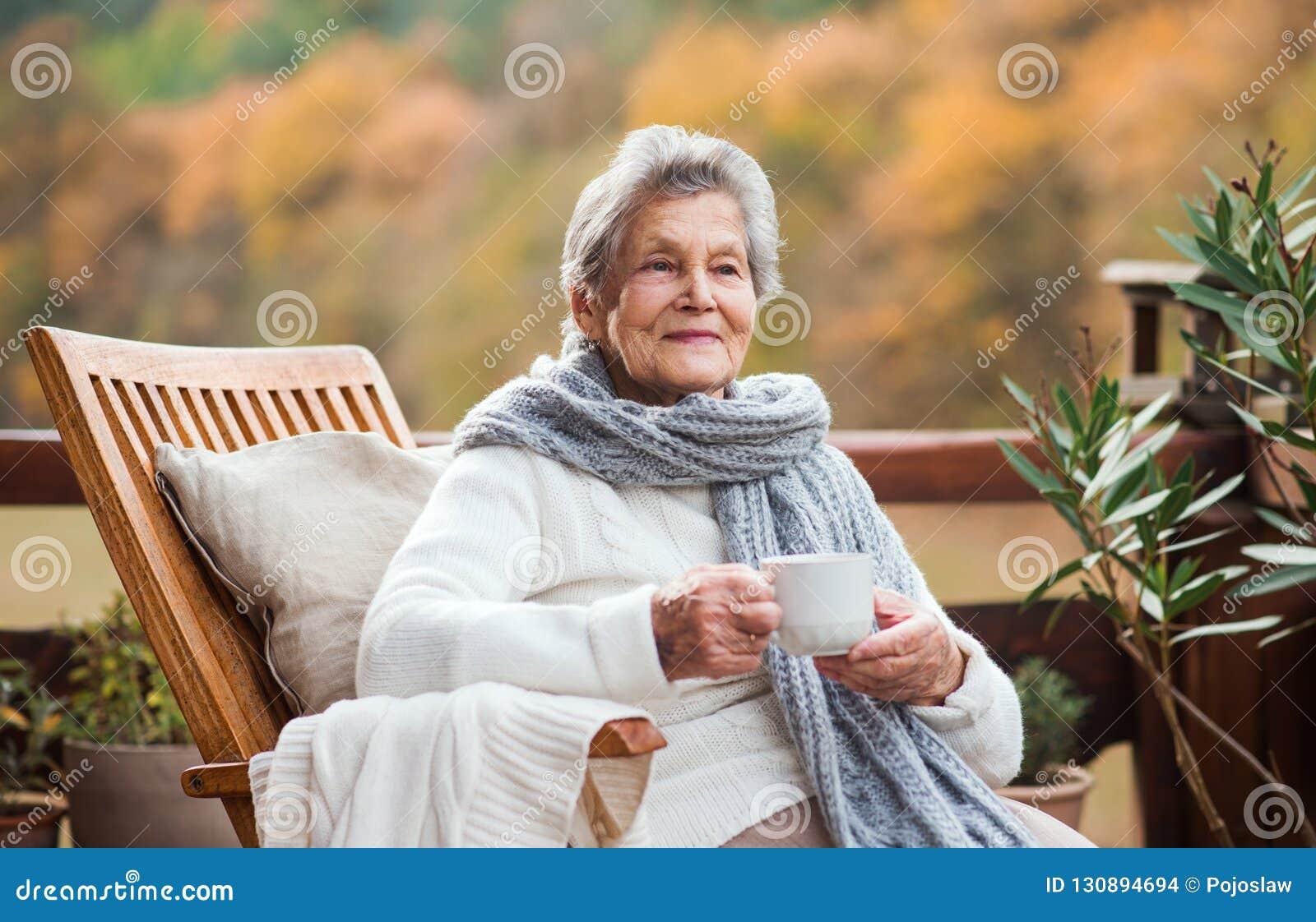 Una mujer mayor que se sienta al aire libre en una terraza adentro en un día soleado en otoño