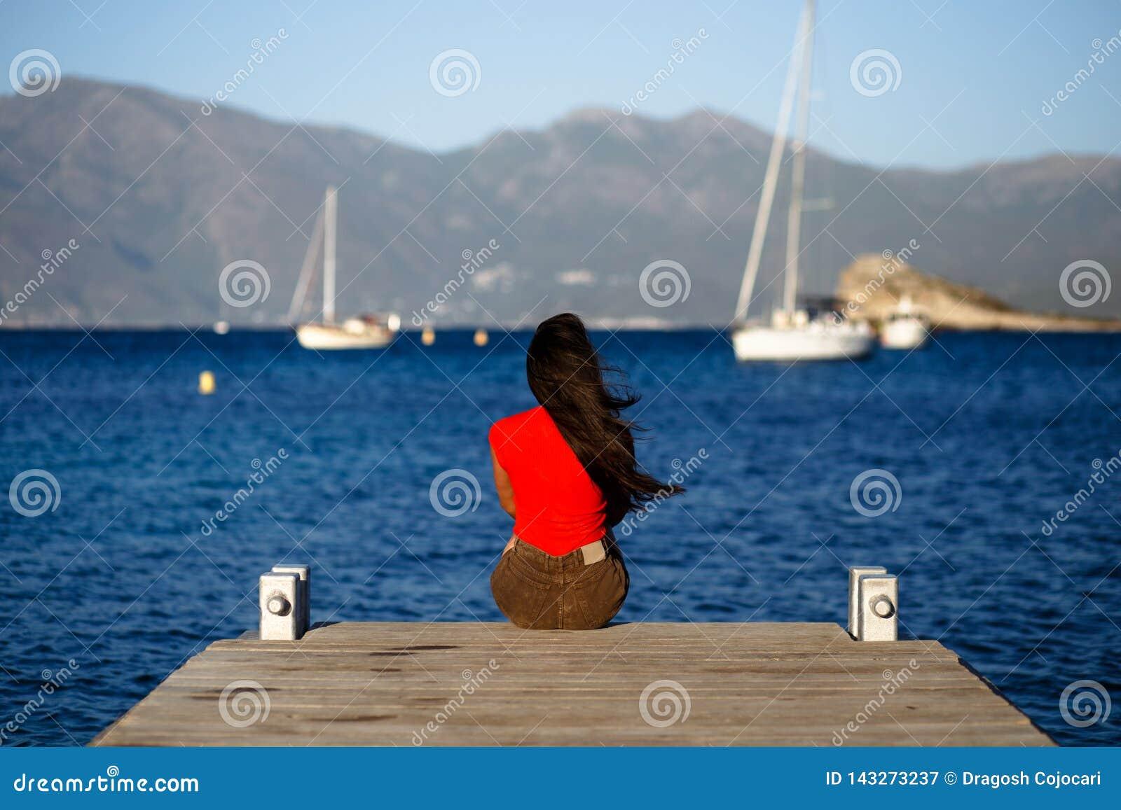 Una mujer morena joven sola en la sentada roja con la parte posterior en el embarcadero de madera, admirando el paisaje marino de