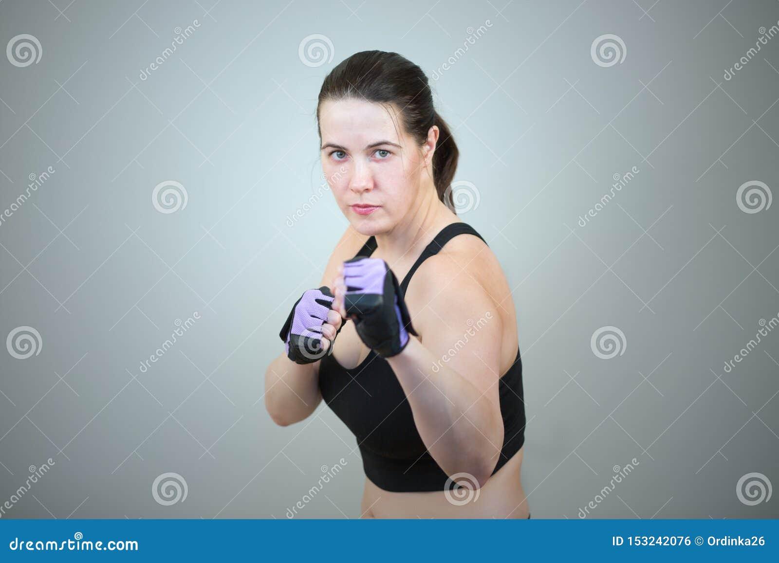 Una mujer practica el Taekwondo y se coloca en una actitud de encajonamiento con un puño apretado aislado en fondo gris del estud