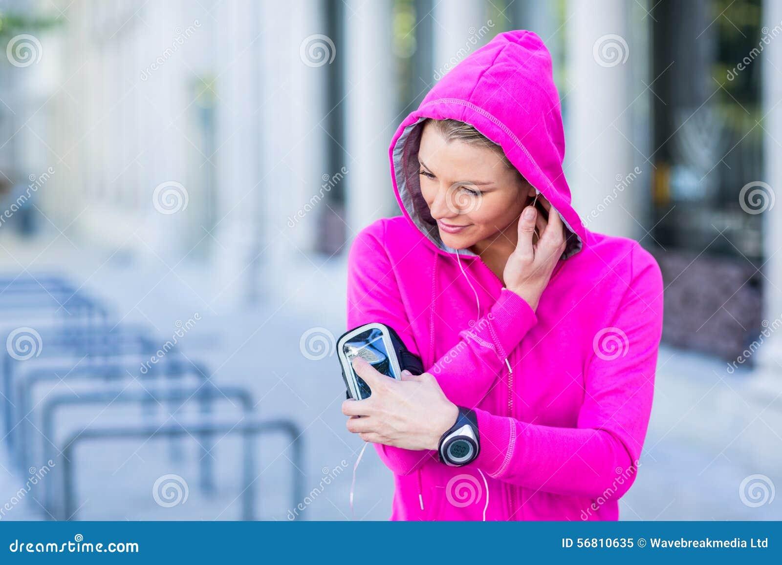 Una mujer que lleva una chaqueta rosada usando su teléfono