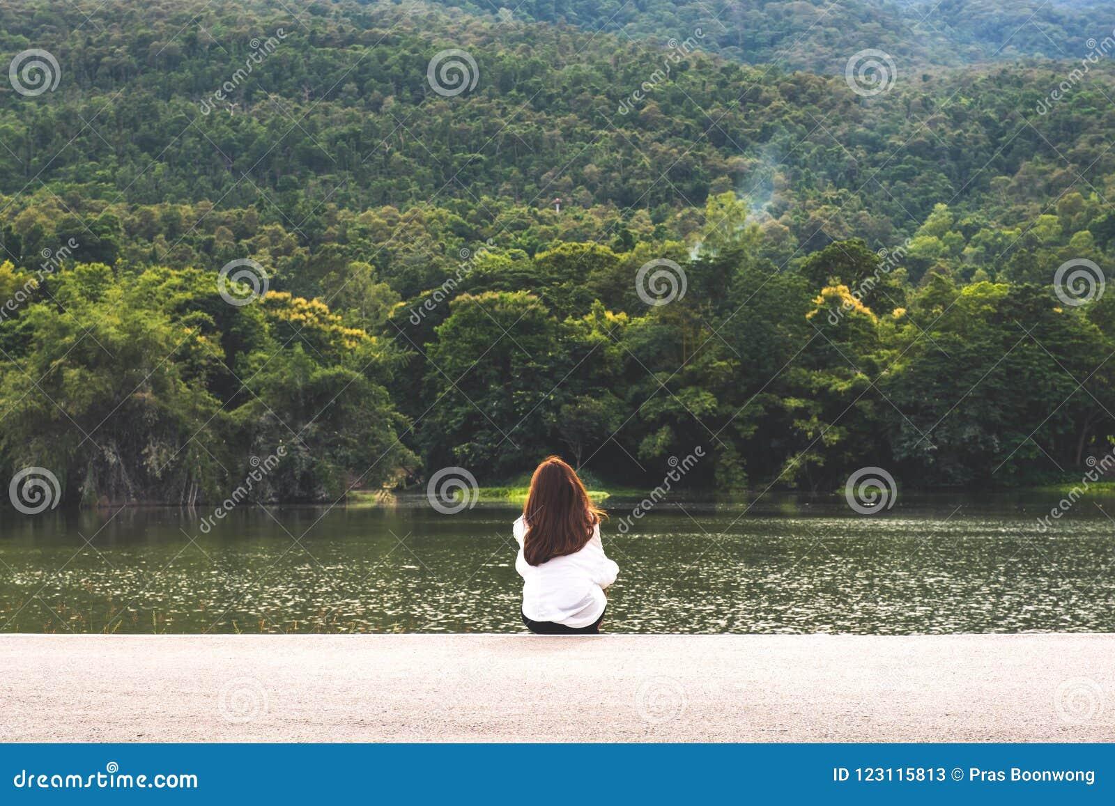 Una mujer que se sienta solamente por el lago que mira las montañas con la naturaleza nublada y verde