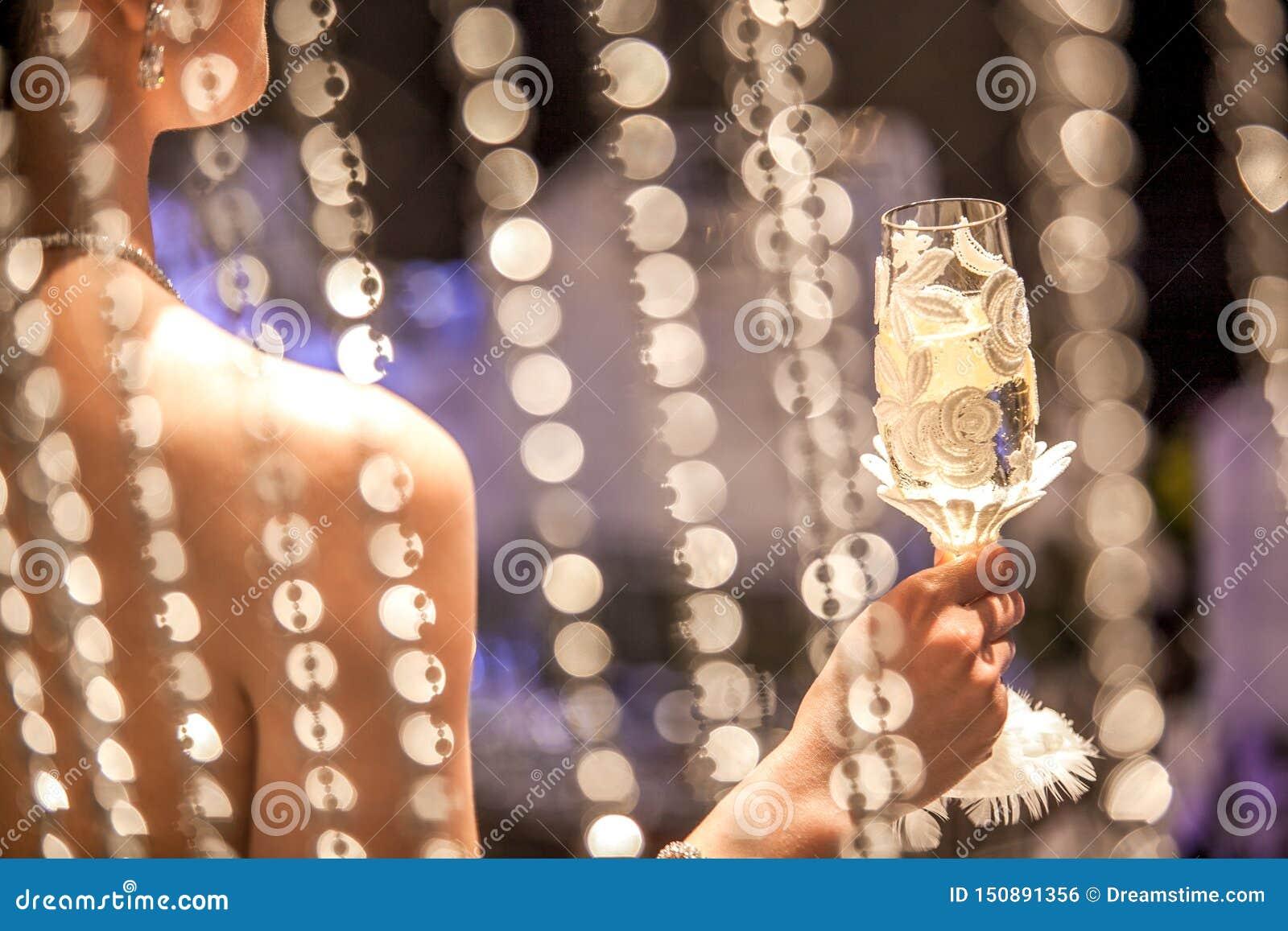 Una mujer que sostiene un vidrio del champán en la recepción nupcial