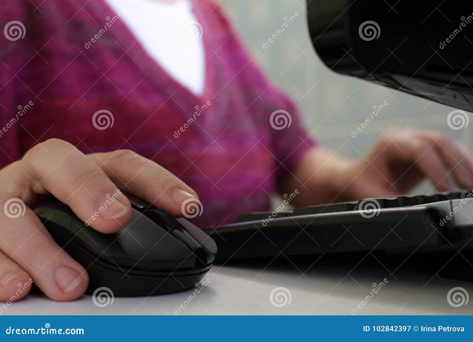 Una mujer que trabaja en un ordenador Mano en el ratón