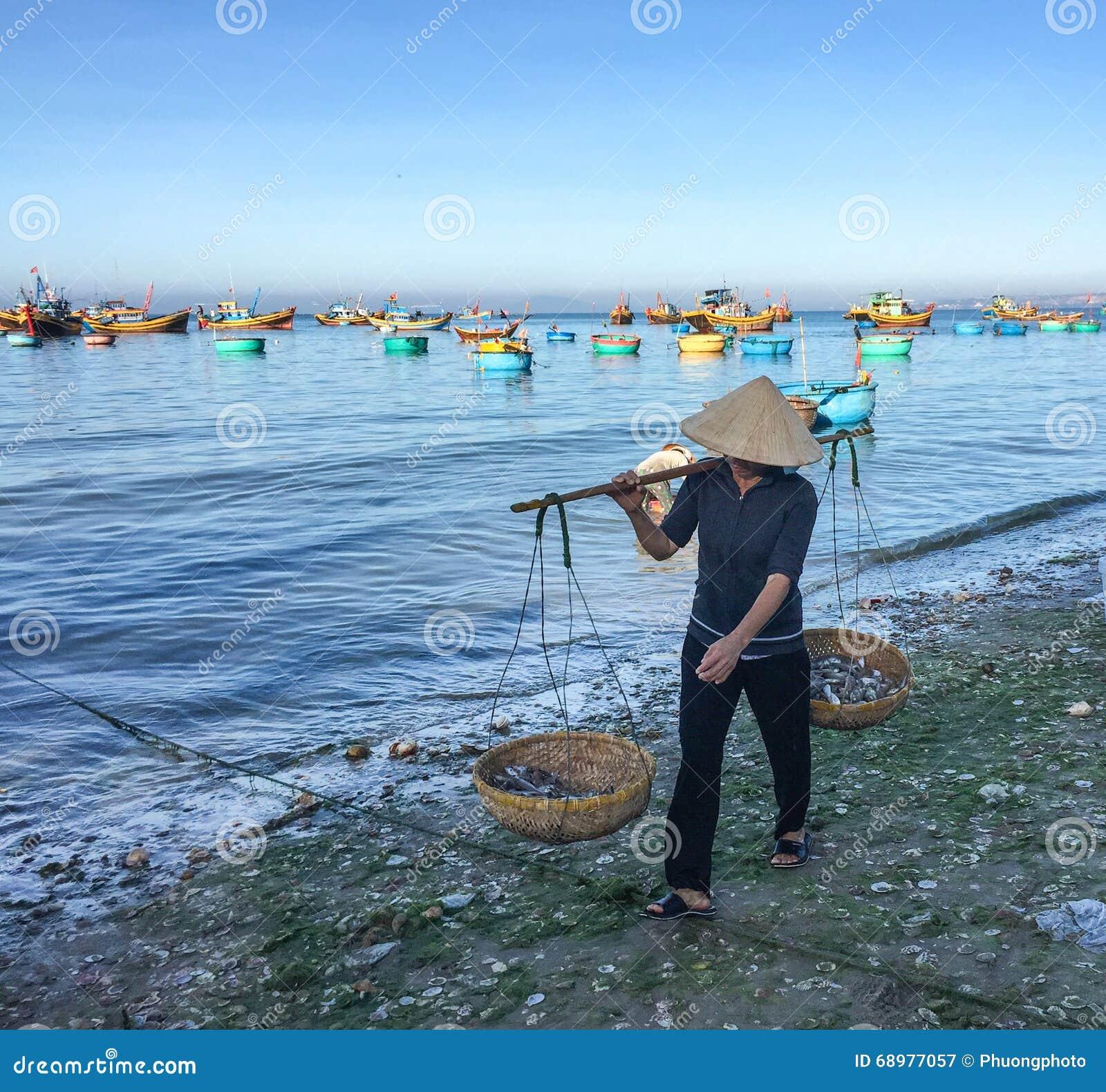 Una mujer que vendía pescados en la playa en Phan sonó, Vietnam