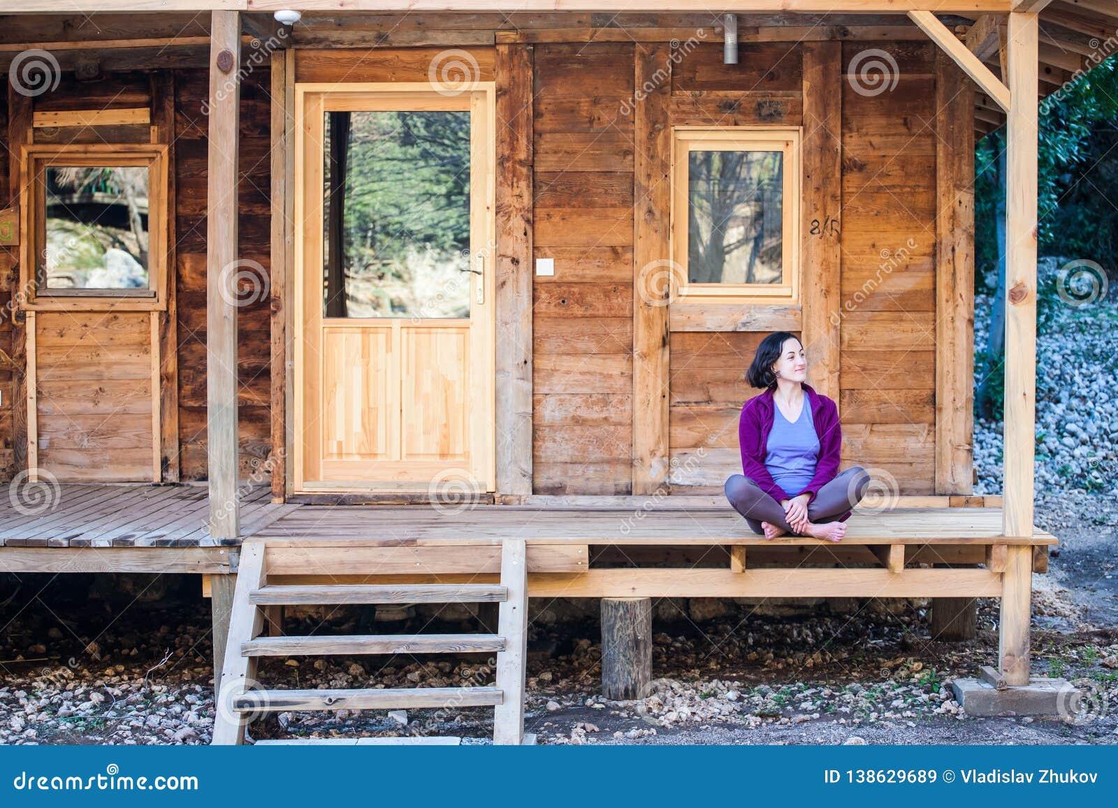 Una Mujer Se Está Sentando En El Pórtico De Una Casa De Madera ...