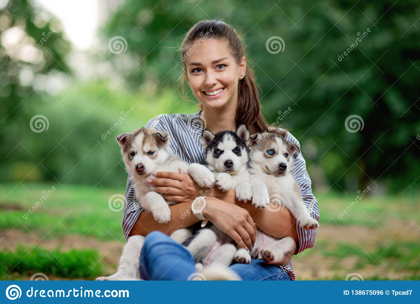 Una mujer sonriente hermosa con una cola de caballo y llevar una camisa rayada está sosteniendo tres perritos fornidos dulces en
