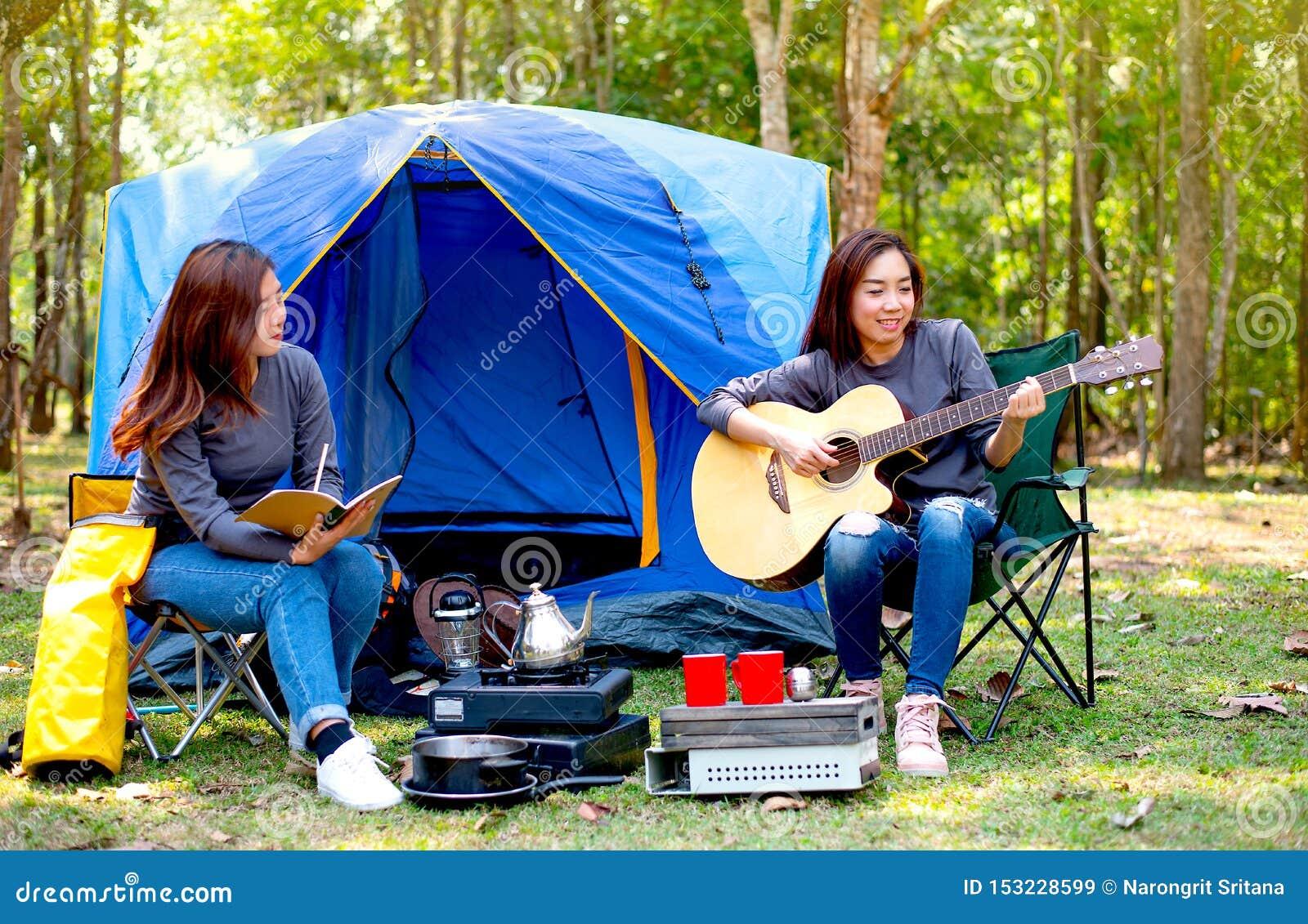 Una mujer tocar la guitarra mientras que la otra registra algo durante acampar en bosque y la mirada como sienten la diversión y