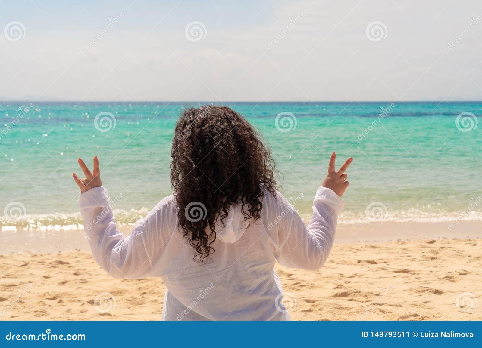 Una mujer valiente joven con el pelo negro rizado largo que muestra los fingeres que hacen la muestra de la victoria contra el ma