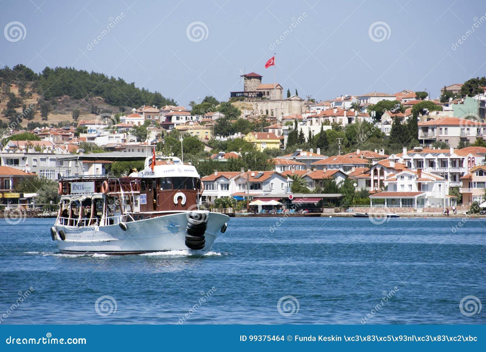 Una nave turística con el molino de viento de piedra en Ayvalik, Turquía