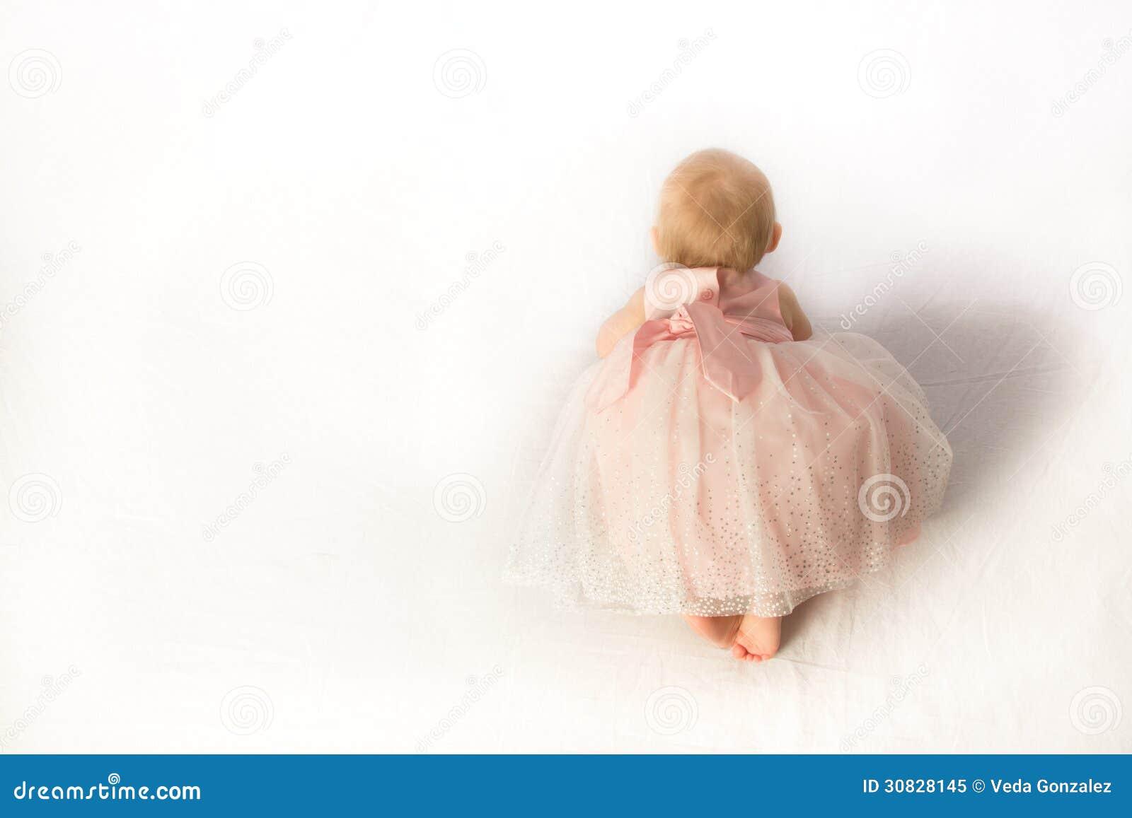 Una neonata strisciante in abito da sera con tanti fronzoli rosa